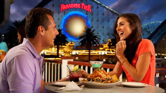 A couple enjoys drinks and food at Cove Bar near California Screamin' in Paradise Pier at night