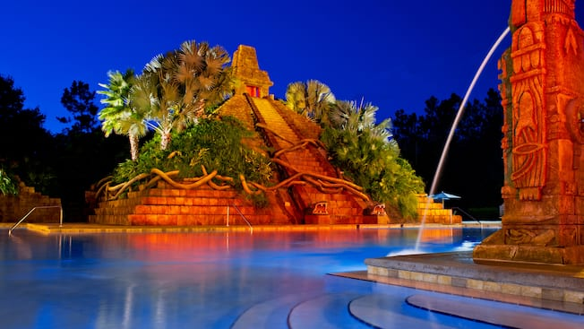 The Mayan pyramid and spouting fountain at the Dig Site pool area, lit up at night