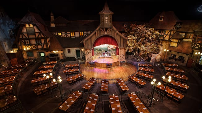 Bird's eye view of the dining, dance and stage areas at Biergarten Restaurant with long tables surrounding a wooden stage