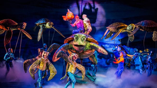 Marlin and sea turtles with their actor counterparts on stage at Finding Nemo - The Musical