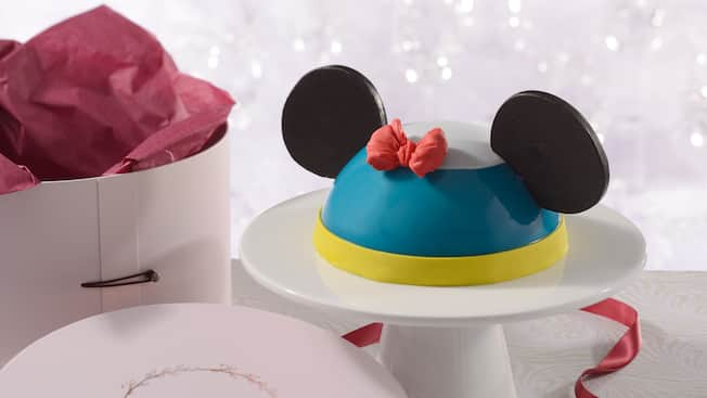 An Amorette's Patisserie Donald Duck dome cake on a pedestal next to its hat box packaging