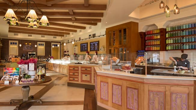 The interior of Amorette's Patisserie with clerks working behind serving counters, round tables with displays of confections out front and, against the rear wall, menu boards, a large wooden cabinet and shelves holding glass jars of jelly beans