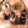 Dos niños con novedosos gorros inspirados en Frontierland leen un mapa con una linterna y un farol pequeño debajo de un tipi temporal en la cama de su hotel