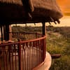 Below a thatched roof, a balcony with a table and chairs overlooks the Resort savanna at sunset