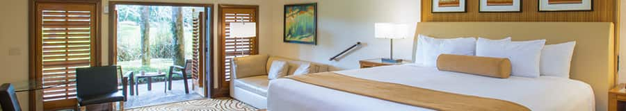 A room with a bed, chairs, a couch, patio and paintings on the wall