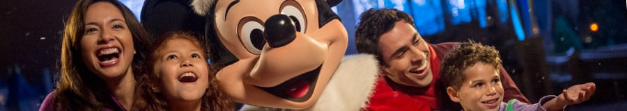Une famille de quatre entoure Santa Mickey devant un Cinderella Castle illuminé pendant les Fêtes