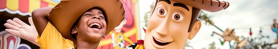 Un jeune garçon portant un t-shirt sur le thème de Woody et un chapeau de cowboy rit alors qu'il interagit avec Woody à l'intérieur de Toy Story Land