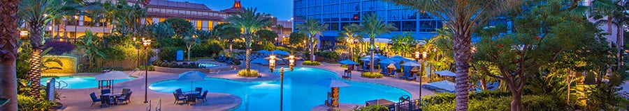 At dusk the pool and hot tub areas glow with ambient lighting below palm trees