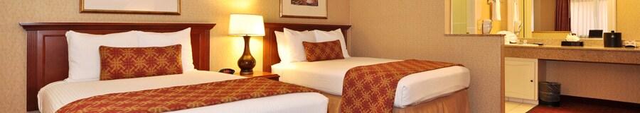 Dos camas matrimoniales con cabeceras de madera, separadas por una mesa de noche, además de un tocador