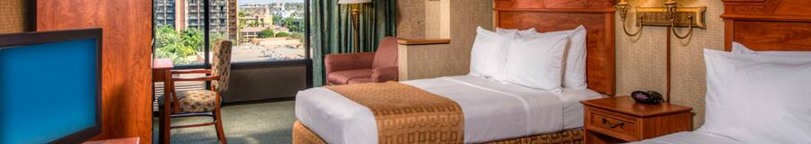 Two double beds with wooden headboards, a TV-dresser, a table and, beyond, an easy chair and window