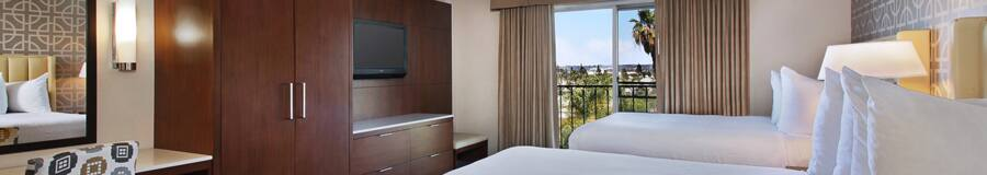 2 queen beds, curtained balcony, contemporary built-in wooden armoire and drawers, wall-mounted TV