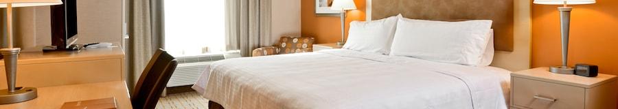 Esta habitación incluye una cama King Size, mesas de noche, lámparas, sillas, un escritorio, una cómoda, TV y arte moderno