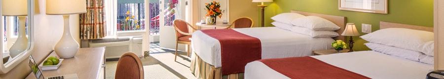 Habitación de hotel con doscamas Queen Size, mesa de noche con lámpara, arte mural enmarcado y una vista soleada desde el balcón