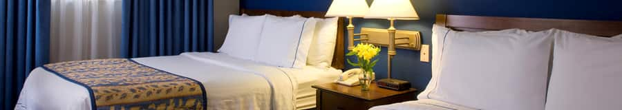 A bedroom featuring 2 queen beds with wooden headboards separated by a nightstand