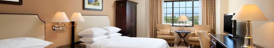 Esta moderna y sofisticada habitación está equipada con tres sillas, un armario, un escritorio, mesas de noche y dos camas Queen Size