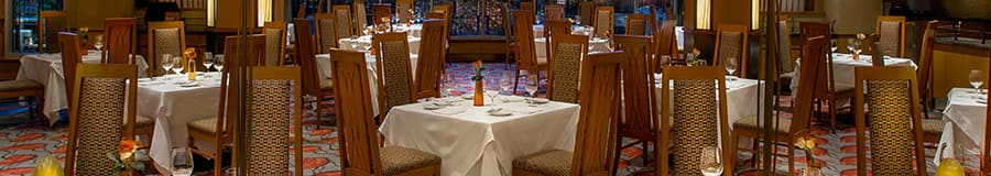 Dining tables for 4 with high back chairs are set and ready for Guests in an elegant dining room