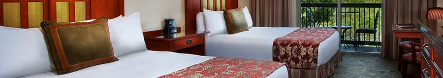 Two queen beds with bed runners, a dresser, desk with a chair and, beyond, a balcony