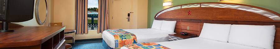2 camas dobles frente a un vestidor con un TV