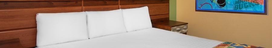 Des oreillers bordent la tête d'un grand lit et une affiche du film «Mighty Ducks» orne un mur à proximité
