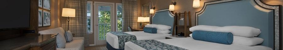 Duas camas queen, uma escrivaninha, Cômoda com TV, sofá-cama e, atrás, uma sacada