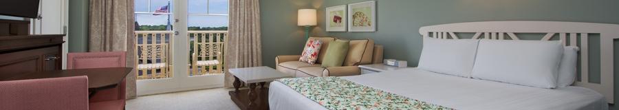 Un grand lit et, au-delà, une table de nuit, un canapé-lit double et une table basse