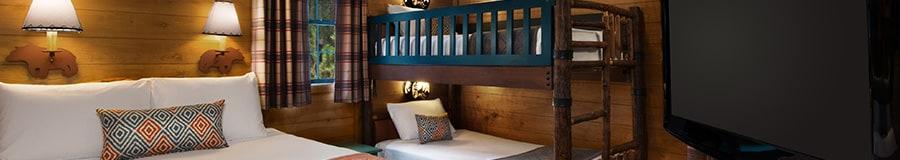 Un TV de pantalla plana, una cama Queen Size, 2lámparas de pared decorativas y un conjunto de literas
