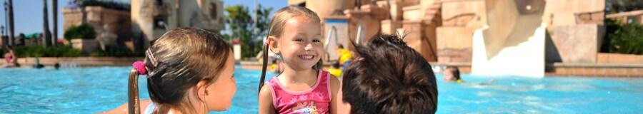 Un par de niñas disfrutan de la piscina junto a su padre en el Caribbean Beach Resort