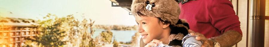 Un niño con un novedoso sombrero de piel de mapache mira desde el balcón de su habitación acompañado de su padre
