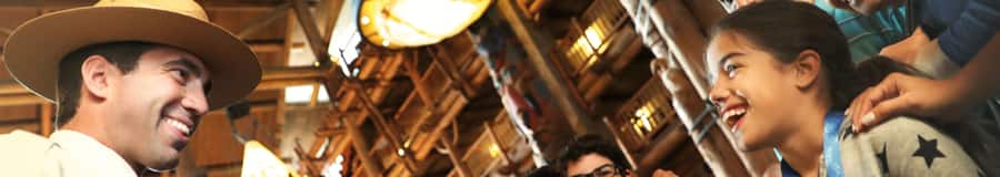 Um funcionário da Disney cumprimenta uma menina e a família dela no saguão