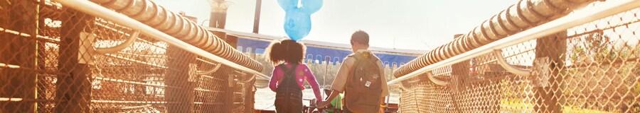 Una niña con un globo con orejas de Mickey sostiene la mano de su hermano mayor mientras cruza un puente
