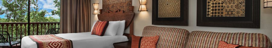 A sofa, decorative pillows, 3 pieces of wall art, 2 sconces, a bed and a balcony that looks out to a lush savanna