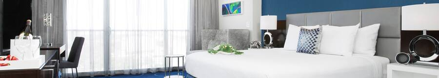 """A room with chairs, a desk, 2 side tables, a TV, a bed with """"The Princess and the Frog"""" plush, 2 lamps and paintings"""