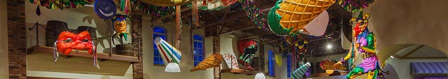 Des masques de Mardi Gras et une série de photos de défilé accrochées aux chevrons d'un plafond haut