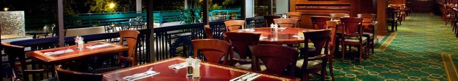 Área de comidas con mesas junto a una pared de ventanas en The Turf Club and Grill