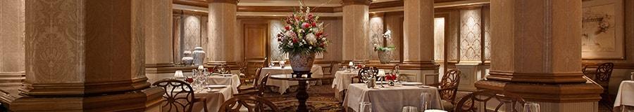 Salle à manger officielle au Victoria&Albert's, avec un bouquet de fleurs et des tables dressées avec des services en porcelaine raffinés