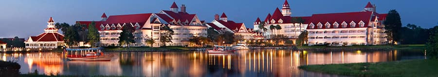 A view of Disney's Grand Floridian Resort & Spa from across Seven Seas Lagoon at dusk