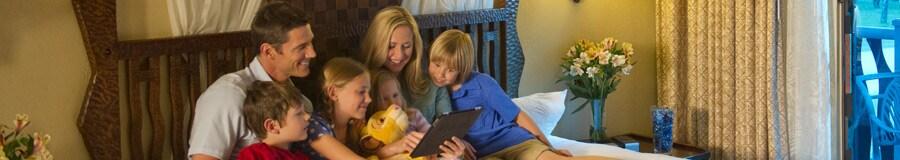 Una familia de 6 en una cama utiliza una tableta digital para planear su día