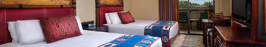 2 camas queen com cabeceiras de madeira ao lado de um pátio