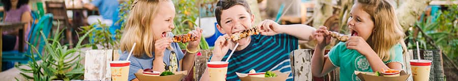 Three kids enjoy kabobs and beverages at an outdoor table