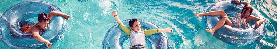 Three kids float on inner tubes in a pool