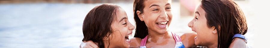 Tres chicas preadolescentes en una piscina del hotel de Walt Disney World Resort donde se hospedan