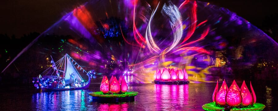 A laser light show illuminates the air above a river, a boat, giant lotus flowers and fountains of water