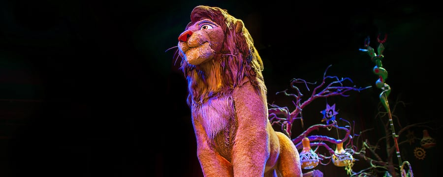 A float depicting Simba near a tree and African folk art