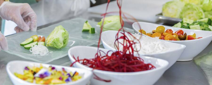 Guests select vegetables and garnish from the row of ingredient bowls provided at their prep station