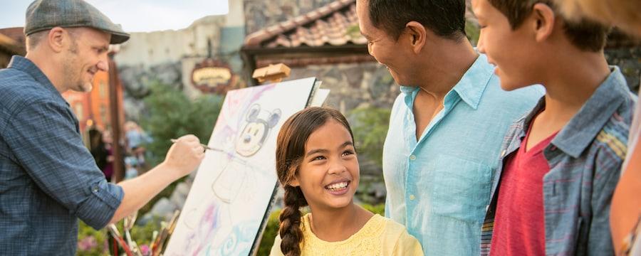 Una niña pequeña sonríe a su familia mientras observa al artista David Buckley pintar una imagen de Mickey Mouse