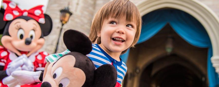 A Minnie Mouse ao lado de um menino segurando um boneco do Mickey Mouse