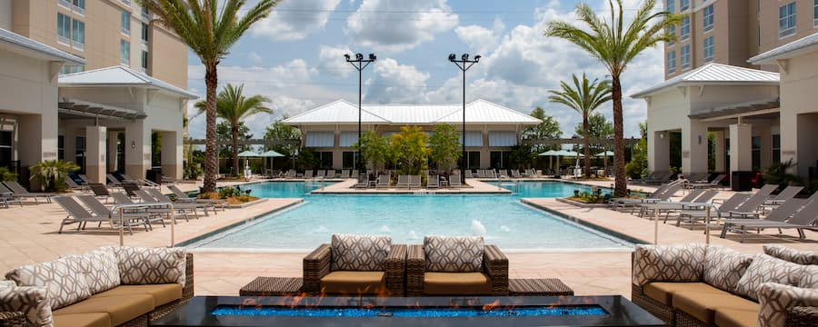 A swimming pool with outdoor recliners, a firepit and stylish outdoor couches