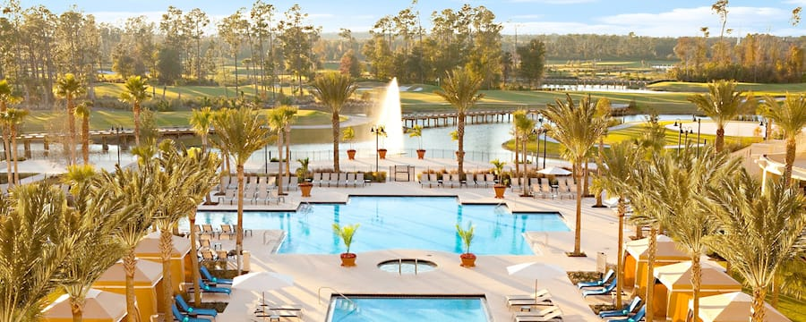 A series of swimming pools leads to a golf course with a large lake at a resort.