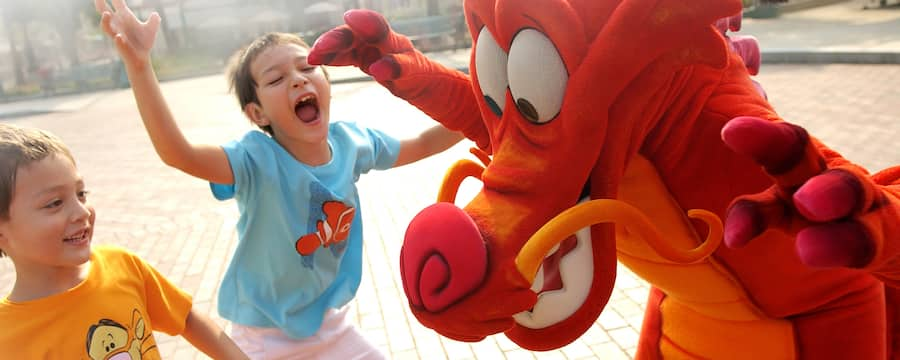 A young Guest runs to hug Mushu, the guardian dragon from Mulan