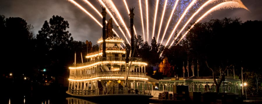 Fireworks above a riverboat that has decorative lighting
